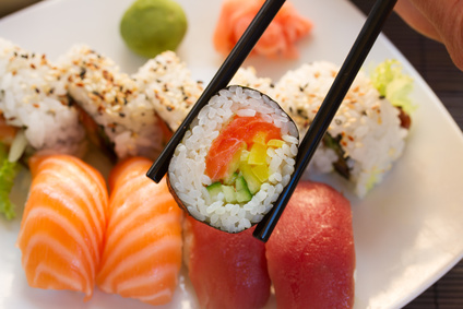 lunch with japaneese  sushi dish  with roll in chopsticks close up