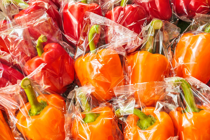 28381731 - bunch of plastic wrapped orange and red bell peppers